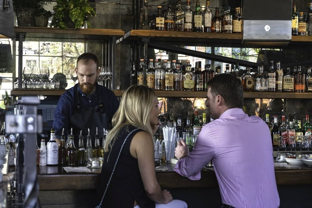 A well-dressed man and woman sit at a well-stocked and trendy bar in West Midtown, with a bartender behind the counter.